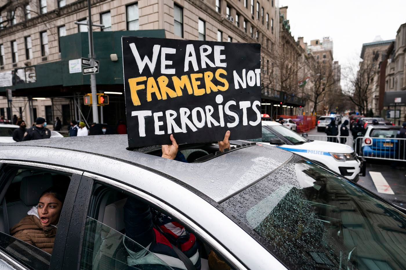 """Indian farmers hold sign """"we are farmers not terrorists"""""""